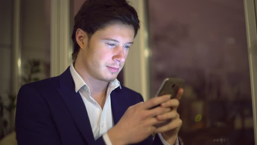 Portrait young man using smartphone at night. Handsome guy wearing in white shirt messaging indoors. | Shutterstock HD Video #25354994