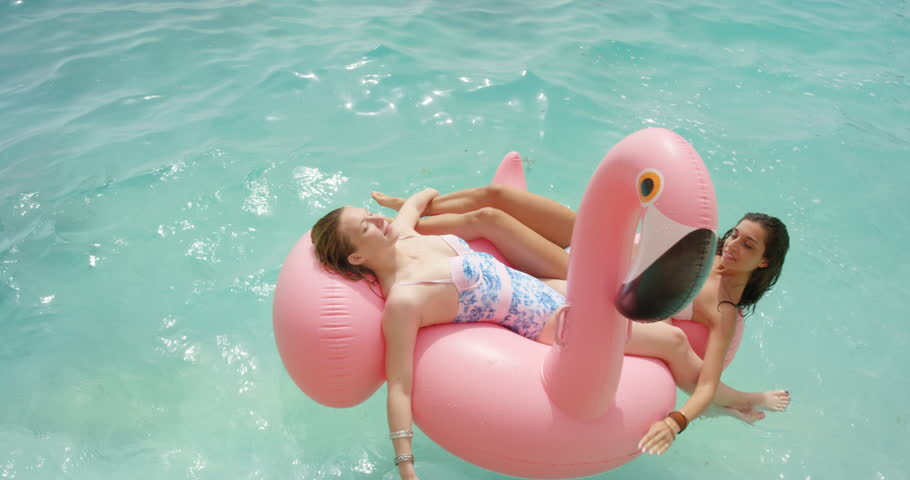 Two girls lying on inflatable flamingo Best friends having fun relaxing floating in clear blue ocean Happy Women enjoying summer vacation on tropical island holiday