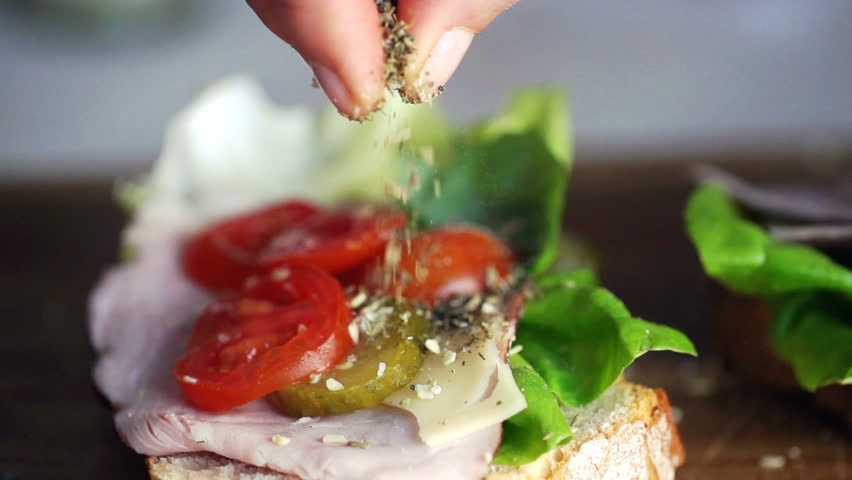 hand adding seasonings on the sandwich, super slow motion