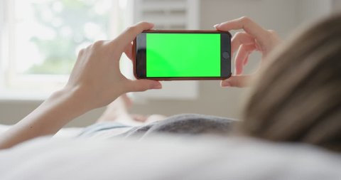 Close up Woman holding smartphone green screen chroma-key greenscreen sharing authentic social media