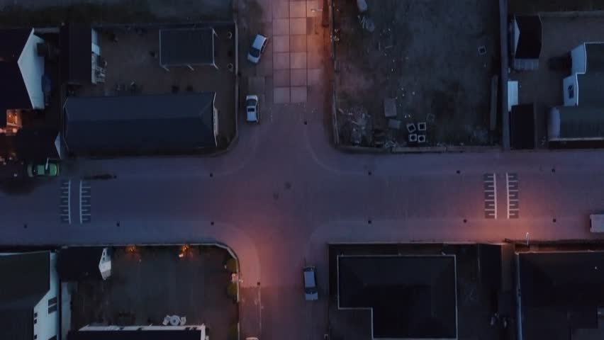 Aerial night flight top down view over trailer park semi-permanent or permanent area for mobile homes showing dark neighborhood with some light from street lights and also car wrecks on the streets 4k