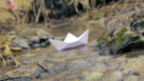 Woman's hand putting paper boat on the water and pushing it away. Paper boats adrift in the river. Origami paper boat sailing from winter to spring. Kazakhstan