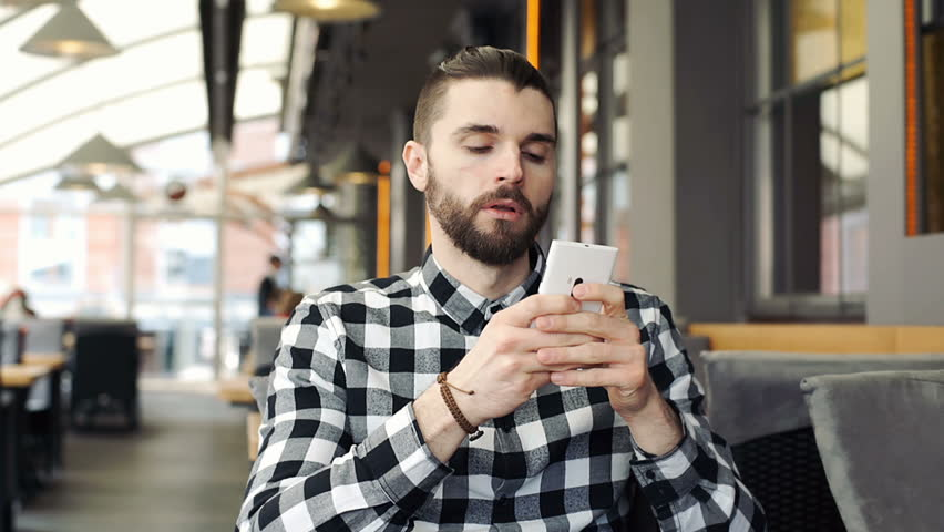 Handsome man looks thoughtful while texting messages on smartphone, steadycam shot  | Shutterstock HD Video #25486484