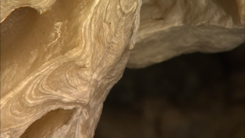Pan across growth rings in broken stalactite in cave
