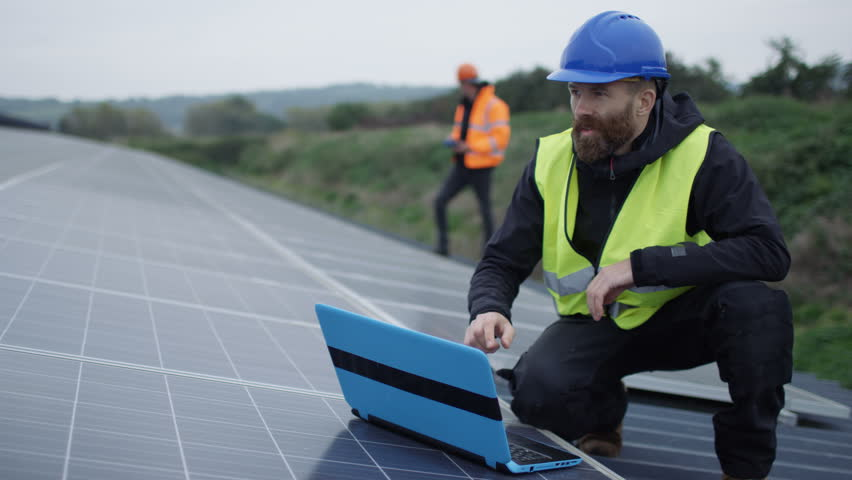 4K Technician with laptop checking the panels at solar energy installation