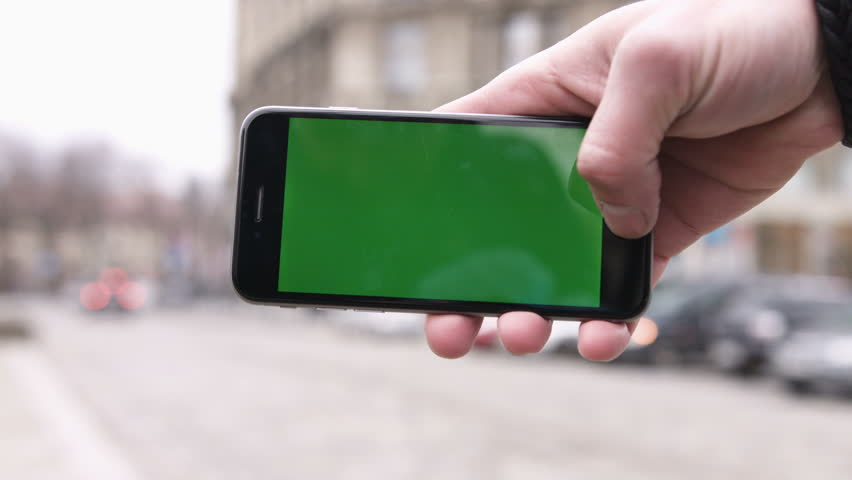 Closeup man hands holding phone with horizontal green screen in the background moving car | Shutterstock HD Video #25491104