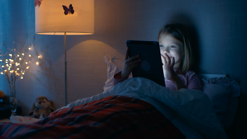Cute Little Girl in Her Bedroom Lies in Bed With Tablet Computer. She Plays in Something. Shot on RED EPIC-W 8K Helium Cinema Camera.