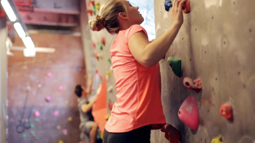 Fitness, extreme sport, bouldering, people and healthy lifestyle concept - young woman exercising at indoor climbing gym wall   Shutterstock HD Video #25542074