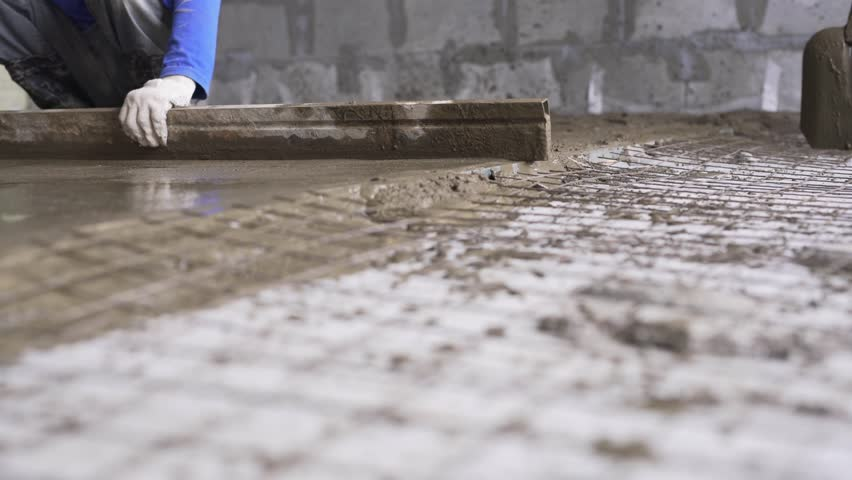 Worker making cement screed on the floor view #25555898