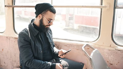 A bearded man writes a message on a smartphone and smokes an e-cigarette in a public transport