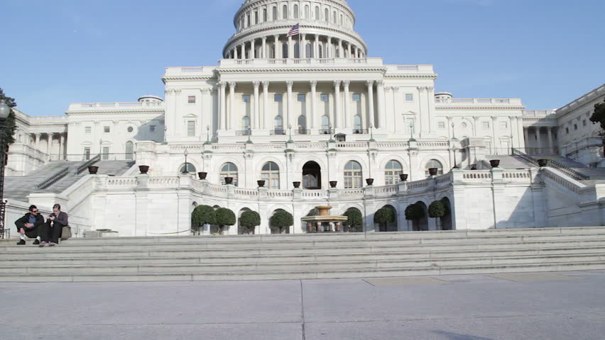 Washington DC, USA - October 23: United States Capitol in Washington DC, USA, home of Congress, the House of Representatives and the US Senate. Tilt shot, tourists sit on the steps.