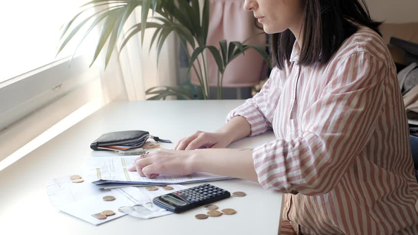 Young brunette woman in striped shirt sits at table next to window and counts her household bills looking at numbers in papers and using scientific calculator to check total sum. | Shutterstock HD Video #25581164