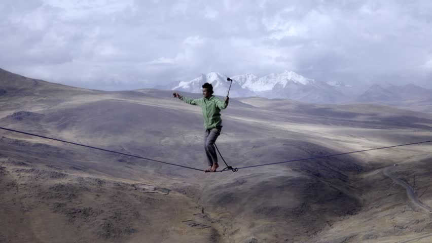 Slackliner balancing on tightrope between two rocks, Snowy mountains of the Huascaran park on the background, Peru. Slow motion