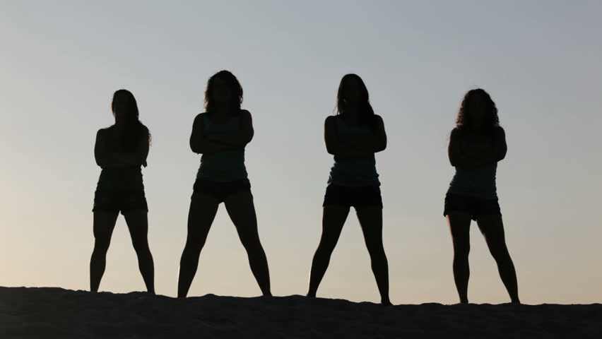 Carefree women dancing in the sunset on the beach