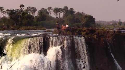 Crazy people diving in the Devil's Pool at Victoria Falls - remote view from the opposite side (Zimbabwe) - HD1080