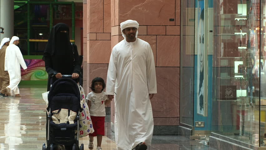DUBAI, UAE - CIRCA 2008: View of an Emirati family, a couple with a little girl, walking together in the souq at Dubai Festival City Mall.