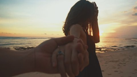 Young couple holding hands woman leading boyfriends walking towards sunset on empty beach. travel concept