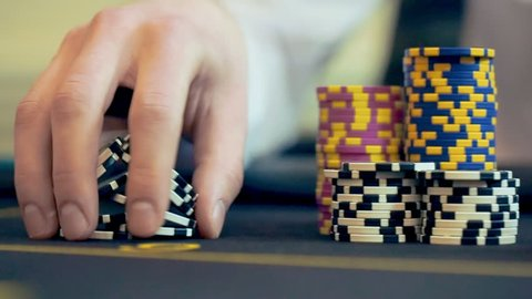 Casino: Man playing poker, excited, turns casino tokens in hand. Close up slow motion