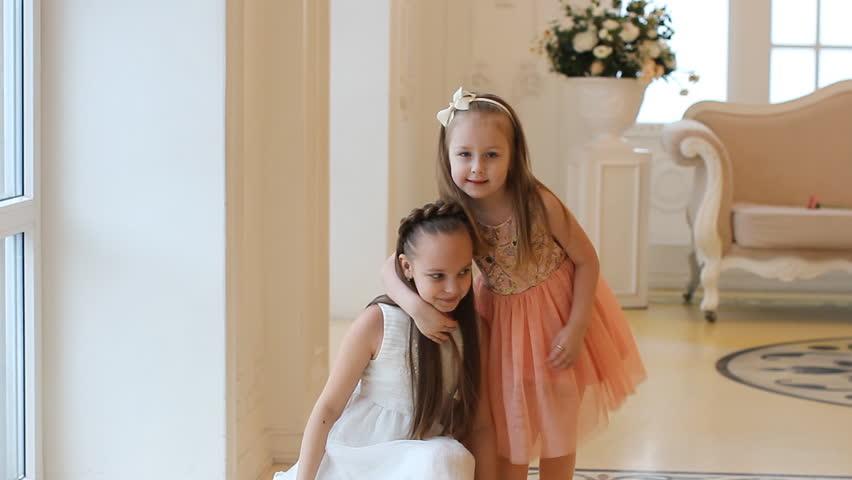 Little girls look out the window, hug and laugh. Sisters in elegant dresses in a beautiful house look out the window.