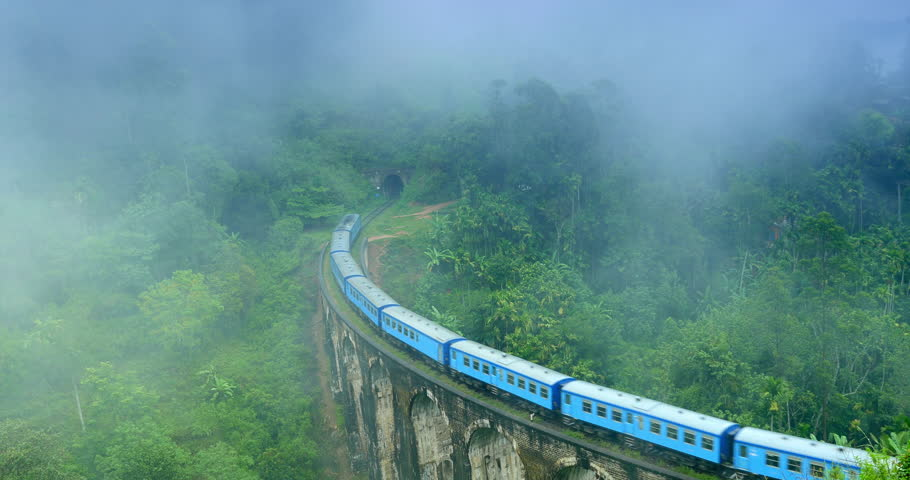 Train crossing Nine Arches Bridge and enters tunnel in foggy morning with clouds of mist above mountains overgrown with green tropical forest in Ella Sri Lanka #25657604