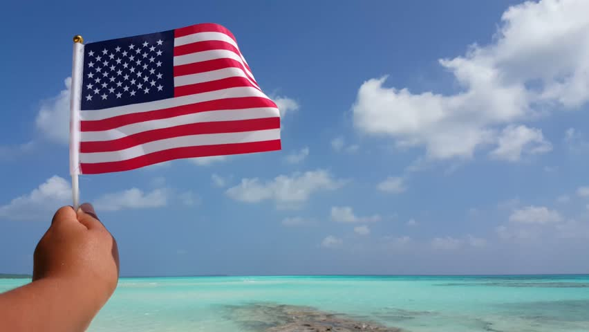 V01661 Maldives Beautiful Beach Background White Sandy Tropical Paradise Island With Blue Sky Sea Water Ocean 4k Hand Holding Us Usa American Flag
