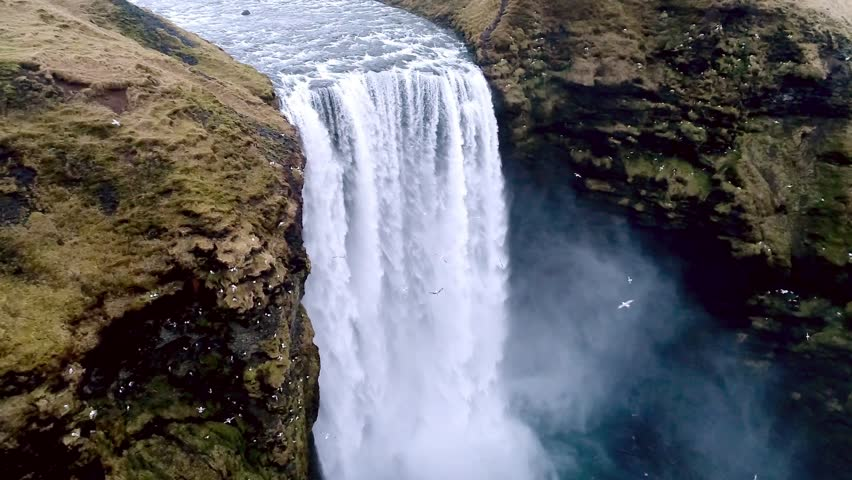 Aerial flight with drone over the famous  Skogar waterfall in Iceland. It is located on the South of the island. Image taken with action drone camera causing distortion and blur. Slow motion shot | Shutterstock HD Video #25673324