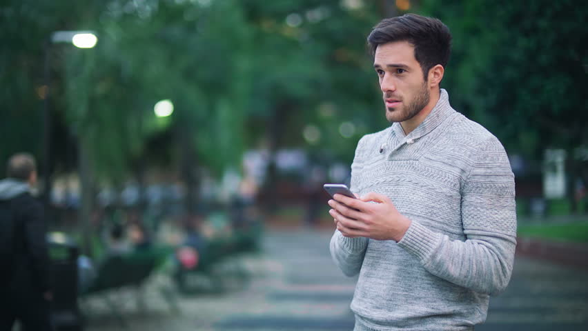 Handsome young man using smartphone in a city park. He is checking mails, chats or the news online. | Shutterstock HD Video #25680254
