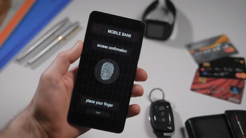 Safe and fast internet access, mobile banking with finger scanning. The application on the smartphone, the man applies his finger to the scanner, the program allows access to the accounts.