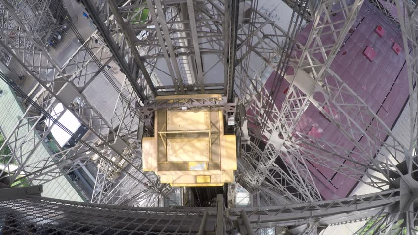Eiffel Tower Elevator Passing Passengers ride the double deck elevator towards the top of the Eiffel Tower in this unobstructed view.