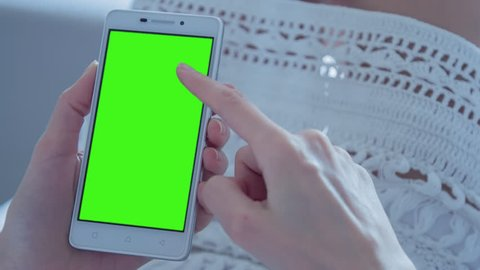 Young Woman laying on a couch uses SmartPhone with pre-keyed green screen. Few types of motion - scrolling up and down, tapping, zoom in and out. Perfect for screen compositing. 10bit ProRes 444