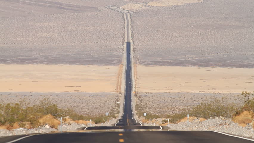 Static Shot of a Long Stretch of Road in the Middle of the Death Valley with Prominent Radiating Heat on the Ground #2570684