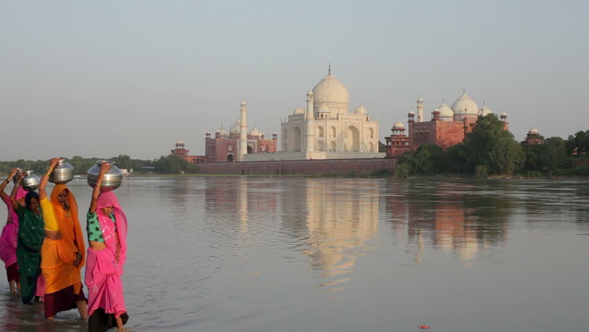 Taj Mahal in the background with women in colorful Saris collecting water