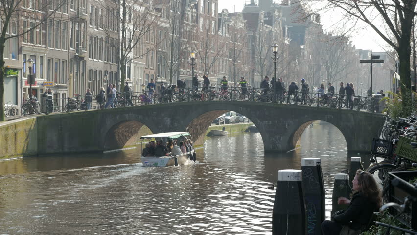 Amsterdam, Netherlands - March 2017. Visitors passing over canal bridge within the Red Light District, Oudezijds Voorburgwal Amsterdam's Red Light District, Amsterdam, Netherlands, Europe