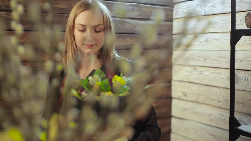 A young florist gathers flowers in a bouquet | Shutterstock HD Video #25727564