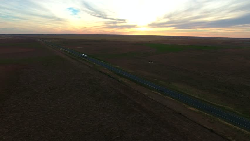 Aerial scene of outback highway or open road on dusk (sunset) with truck (lorry) (Semi-trailer) traveling on rural country high speed freeway.