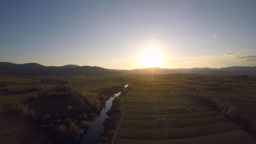 Aerial flight over a marsh at sunset