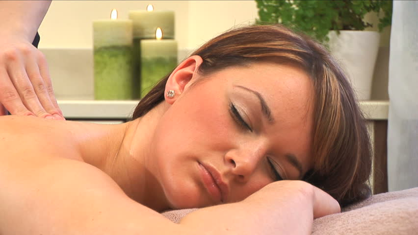 Beautiful brunette girl relaxes during massage at the health spa