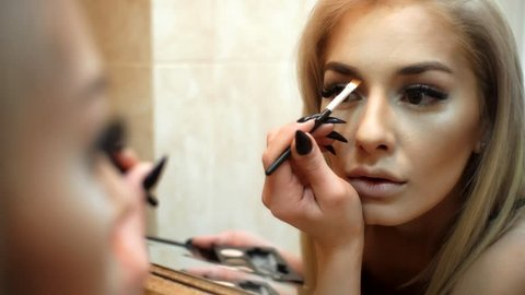 Mirror reflection of woman paints her eyebrows. Beautifull girl