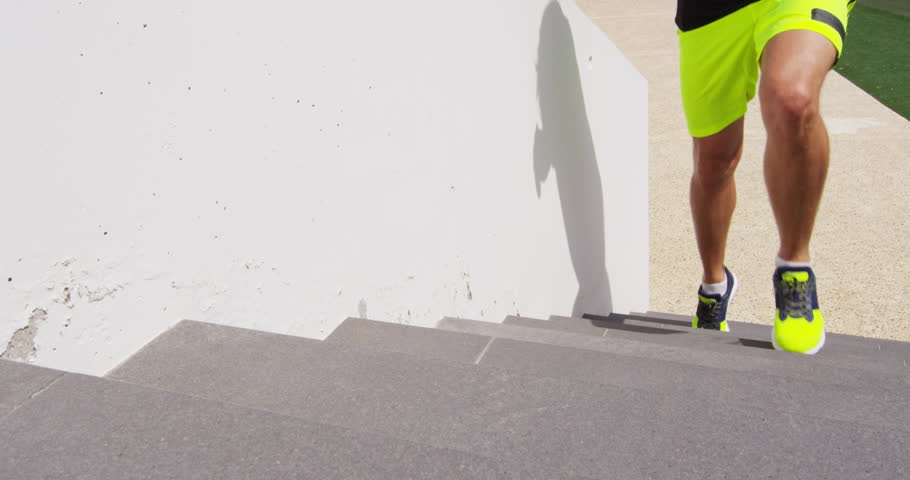 Running on stairs man doing run up on staircase. Male runner athlete climbing stairs in sport workout run outside. RED EPIC SLOW MOTION.