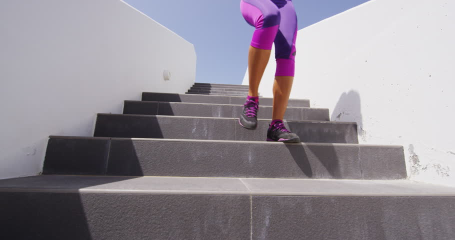 Runner running down stairs. Woman exercising jogging outdoors doing run down stairs.