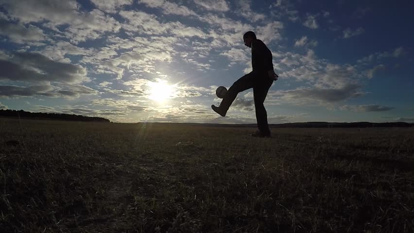 Soccer. Man is stuffing a football soccer ball sport silhouette at sunset football freestyle | Shutterstock HD Video #25842899