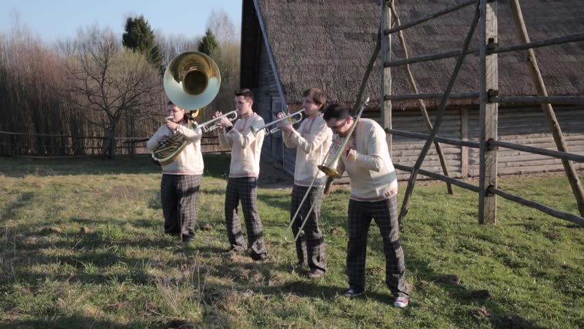 Four musicians make moves to the right and left . Play on wind instruments . Brass Quartet. Synchronous movements of musicians . Wind instrument concert in nature . Concert of musicians in nature .