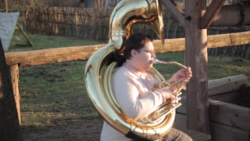 The guy is playing on the tuba. Camera from the bottom up. In a white shirt and brown plaid pants. Swings left and right .Sits on the bench. In plaid pants and a white shirt .