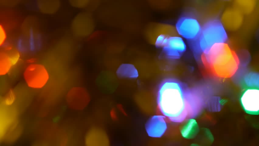 Very blurred tracking shot of Christmas lights and tinsel on a tree