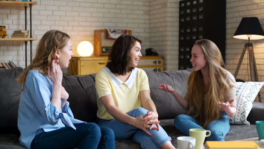 three young and energetic best friend girls talk together emotionally and lively with gestures and bright impression, laugh and smile while sitting on sofa at home during sunny day
