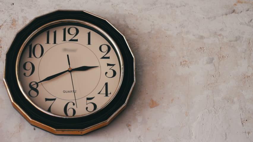 Closeup white clock hanging on wall ticking.Round white clock hanging on a  white wall