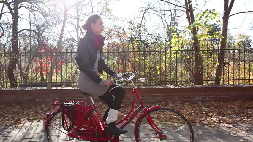 Young woman riding on bike in autumn setting.