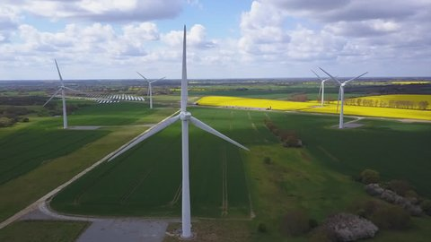 Wind turbines high altitude aerial shot with rape seed fields in background