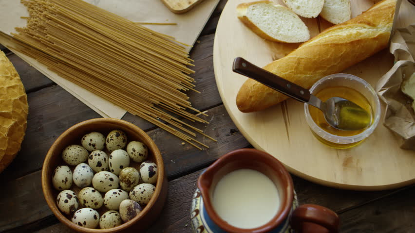 View from above of butter, bread and honey on spinning plate with quail eggs in bowl, milk and homemade spaghetti on wooden table