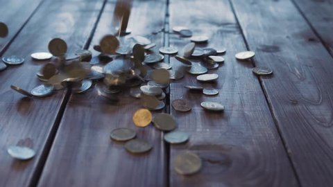 Pile of coins falling on the wooden table. Economic and financial crisis. Salary fall and pension increase, heap or bunch funds for buy for people. Close up of capital indoors. Studio slow motion